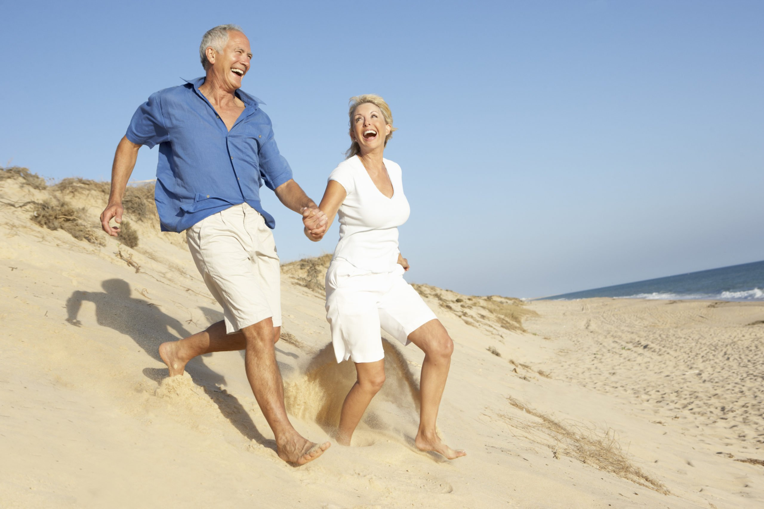 older couple running down a sand dune