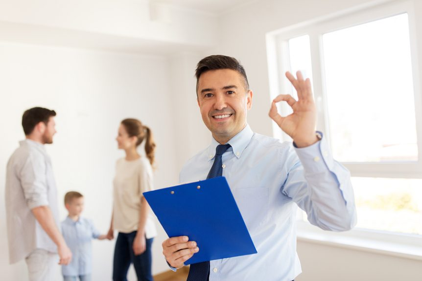 Realtor giving OK sign with family looking at a house
