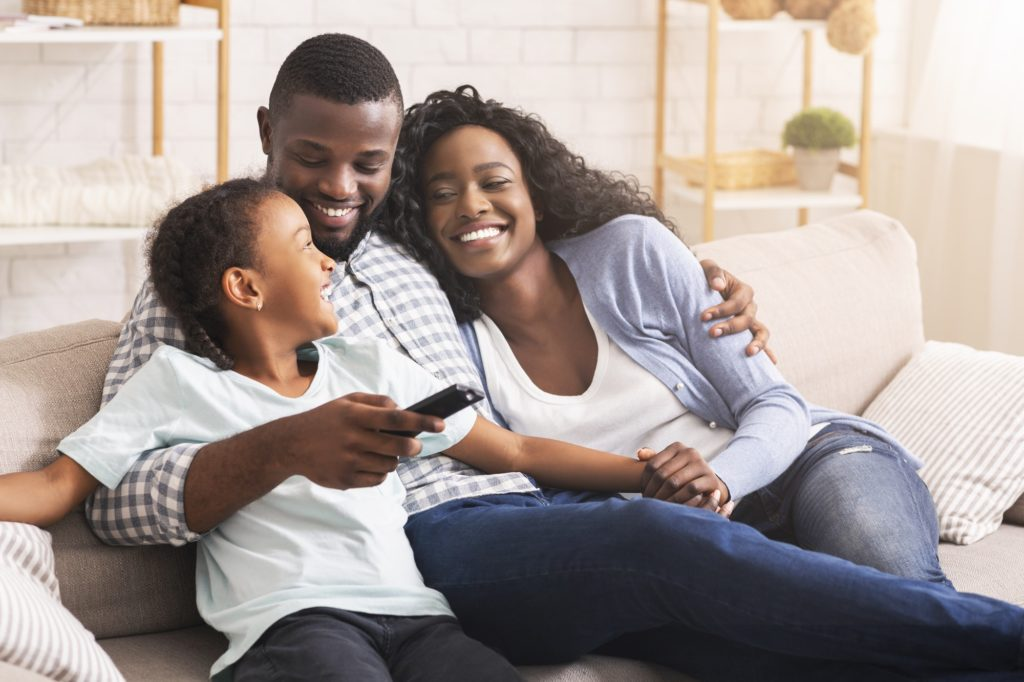 Happy african american family relaxing and watching TV at home