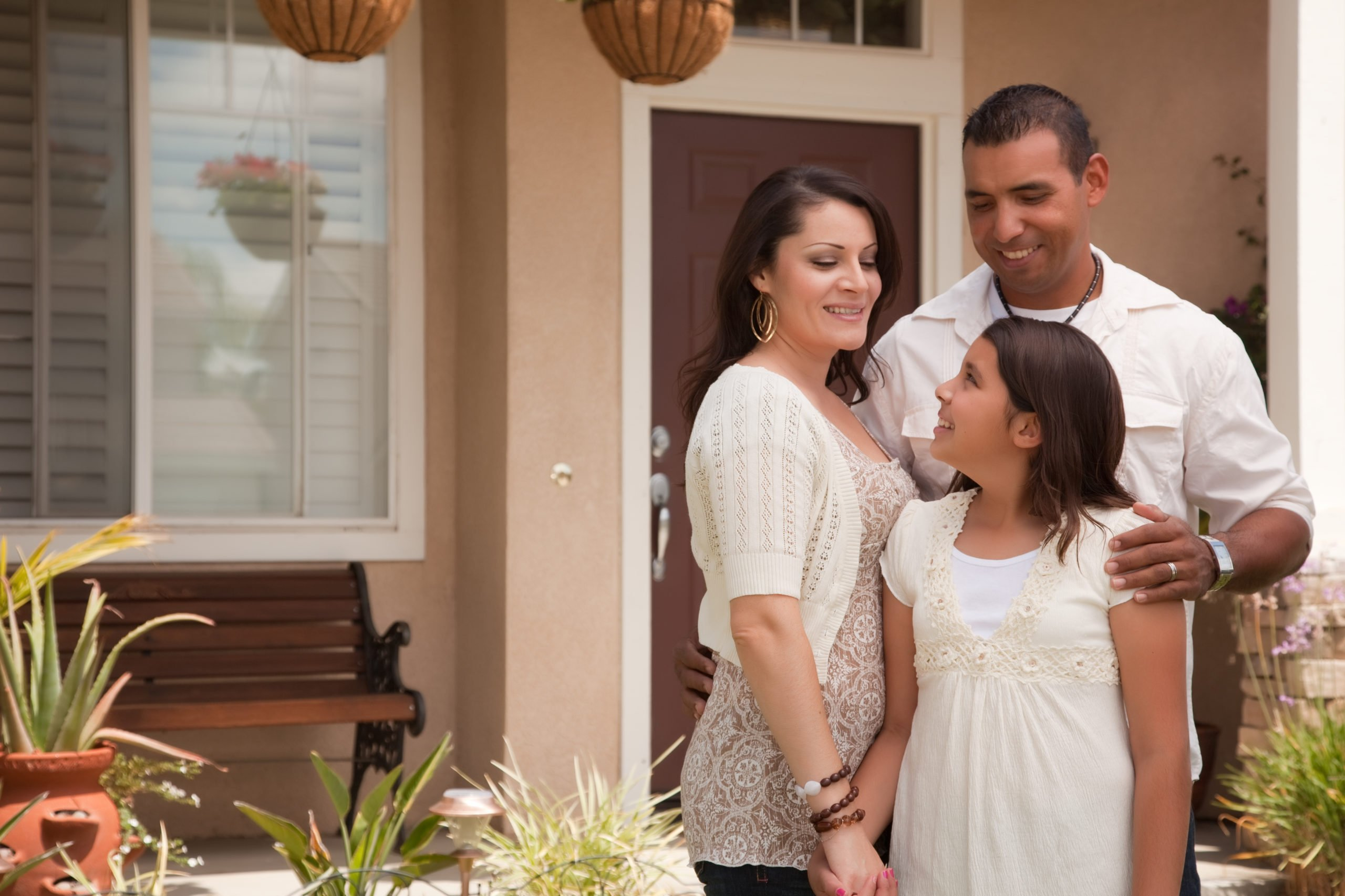 Hispanic family in front of home