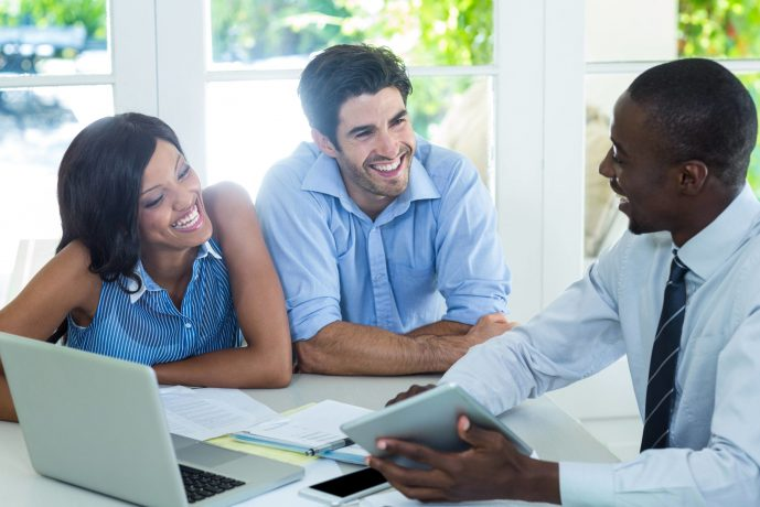 Couple working with loan officer at kitchen table