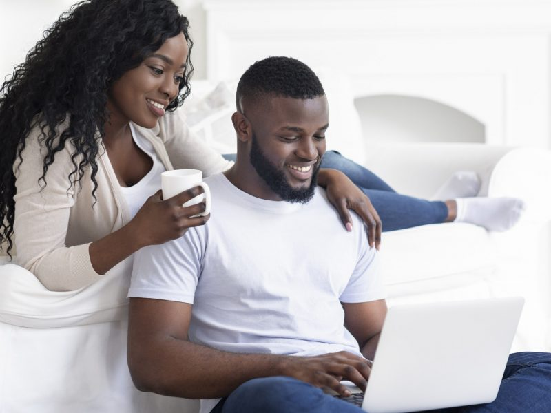 Black couple web surfing on laptop while sitting at home