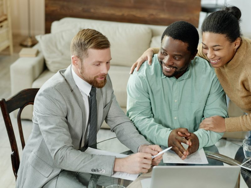 Cheerful couple talking to financial adviser