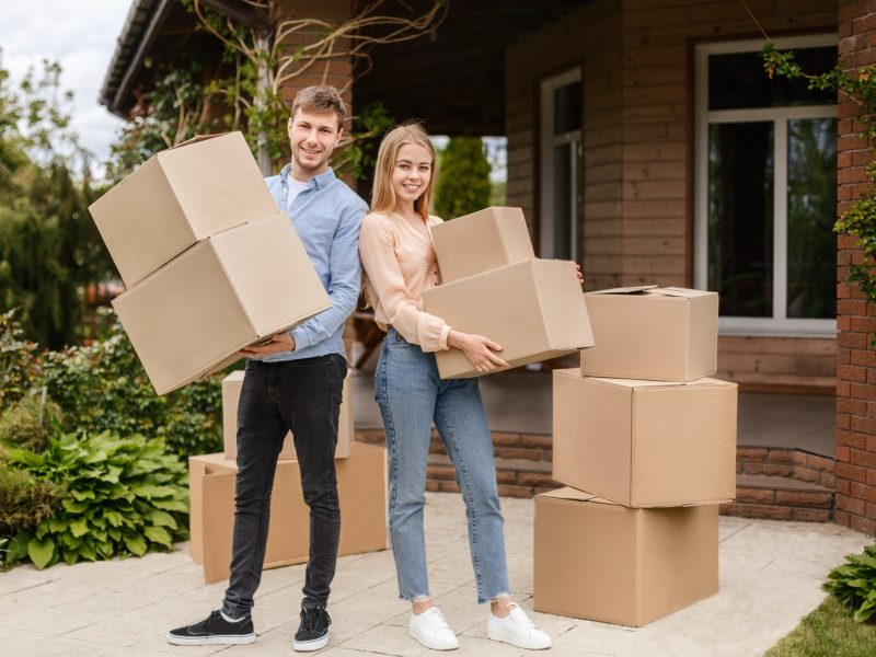 Moving to new house. Young guy with his wife holding cardboard boxes in front of their home