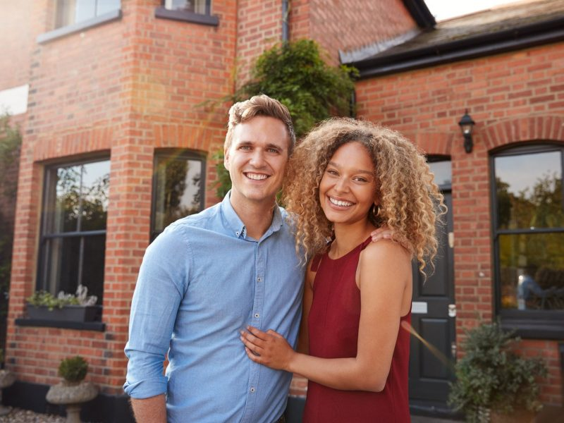 portrait of excited young couple standing outside new home together